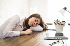 睡觉在她的书桌上的疲乏的妇女 库存照片