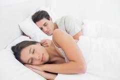 睡觉在她的伙伴旁边的俏丽的妇女 免版税库存照片