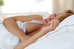 睡觉在她的卧室的美丽的妇女早晨 库存照片
