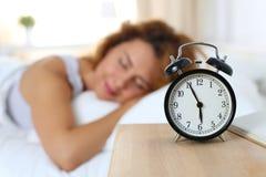 睡觉在她的卧室的美丽的愉快的妇女早晨 图库摄影