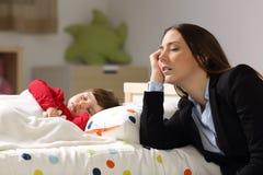 睡觉在她的女儿旁边的疲乏的工作者母亲 免版税库存照片
