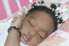 睡觉在她的屋子(一岁)里的可爱的女婴 免版税库存图片