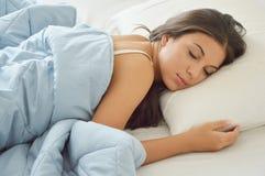 睡觉在她的床上和放松早晨的年轻美丽的妇女 库存图片