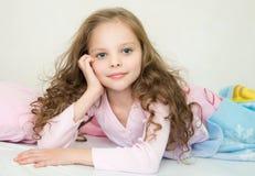 睡觉在她的床上的可爱的小女孩 免版税图库摄影