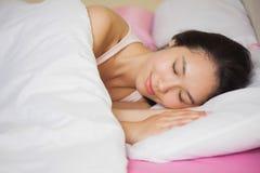 睡觉在她的床上的平安的年轻亚裔妇女 库存照片