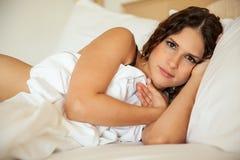 睡觉在她的床上的性感的女孩 库存照片