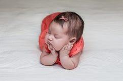 睡觉在她的手肘和手的美丽的新出生的婴孩 库存图片