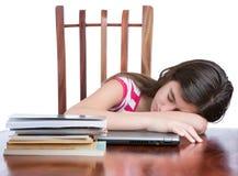 睡觉在她的有堆的膝上型计算机的疲乏的女孩在桌上的书 库存照片