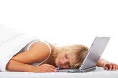 睡觉在她的膝上型计算机的妇女在床上 库存照片