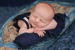 睡觉在小船的微笑的新出生的男婴 免版税库存图片