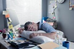 睡觉在工作场所的被用尽的商人 图库摄影