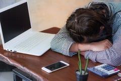 睡觉在工作场所的被用尽的妇女在坚硬工作日以后 库存照片