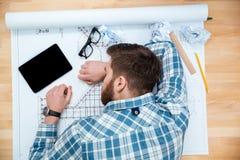 睡觉在工作场所的被用尽的有胡子的年轻建筑师 免版税库存图片