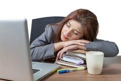 睡觉在工作场所的年轻女商人 库存照片