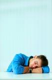 睡觉在工作场所的年轻疲乏的商人 免版税图库摄影