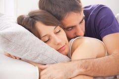 睡觉在床上的一对年轻夫妇的画象 免版税库存图片