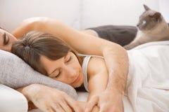 睡觉在床上的一对年轻夫妇的画象 免版税库存照片