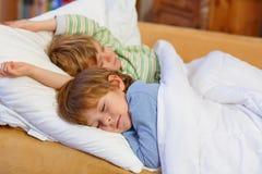 睡觉在床上的两个小白肤金发的兄弟姐妹男孩 免版税库存照片