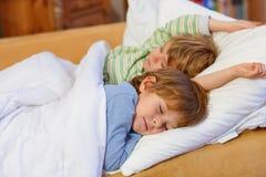 睡觉在床上的两个小白肤金发的兄弟姐妹男孩 库存照片
