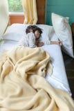 睡觉在床上的亚裔女孩盖用毯子 免版税库存照片