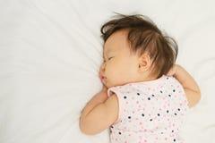 睡觉在床上的亚裔女婴 免版税图库摄影