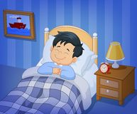 睡觉在床上的动画片微笑小男孩 免版税图库摄影