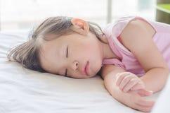 睡觉在床上的女孩在天时间 免版税图库摄影