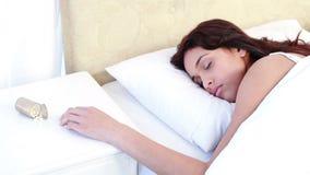 睡觉在床上的妇女由溢出的瓶在桌上的药片 股票视频