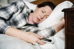 睡觉在床上的妇女,当运载电话时 免版税库存照片
