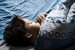 睡觉在床上的小男孩 免版税库存图片