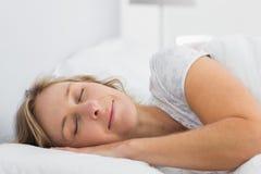 睡觉在床上的平安的白肤金发的妇女 图库摄影