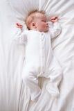 睡觉在床上的新出生的女婴 免版税图库摄影