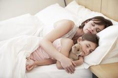 睡觉在床上的母亲和女儿 免版税图库摄影