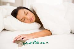 睡觉在床上的浅黑肤色的男人由溢出的瓶药片 库存照片