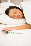 睡觉在床上的浅黑肤色的男人由溢出的瓶药片 免版税库存照片
