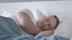 睡觉在床上的灰色头发人