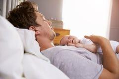 睡觉在床上的父亲拿着新出生的小女儿 免版税库存照片