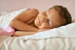 睡觉在床上的逗人喜爱的女孩 免版税库存照片
