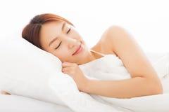 睡觉在床上的年轻亚裔妇女 免版税库存照片