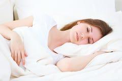 睡觉在床上的年轻秀丽妇女 免版税库存图片