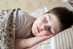 睡觉在床天的男孩画象 免版税库存照片