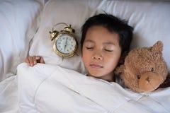 睡觉在床白色枕头和板料的亚裔男孩与闹钟和玩具熊 免版税库存照片