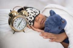 睡觉在床白色枕头和板料的亚裔男孩与闹钟和玩具熊 库存照片