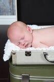 睡觉在手提箱的婴孩 免版税库存照片