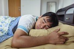 睡觉在早晨时间的床的亚裔人 图库摄影