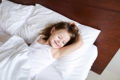 睡觉在早晨的小白种人女孩在床上的学校前与白色亚麻布 库存照片