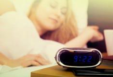 睡觉在时钟和书附近的妇女 免版税库存图片