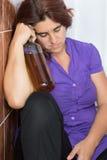 睡觉在有一个瓶的卫生间里的醉酒的拉丁妇女liqu 库存图片