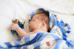 睡觉在有天使图的蓝色毯子的逗人喜爱的新出生的婴孩  库存照片