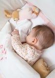睡觉在有安慰者和玩具的一个轻便小床的女婴 图库摄影